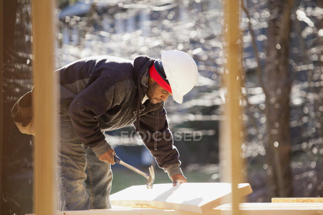 Carpenter a hammer lifting rafter for house construction — Stock Photo