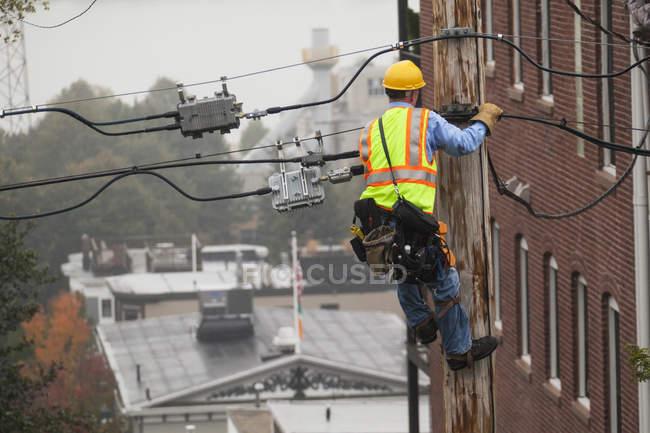 Канатоходец с помощью лайнсменов залезет на столб — стоковое фото
