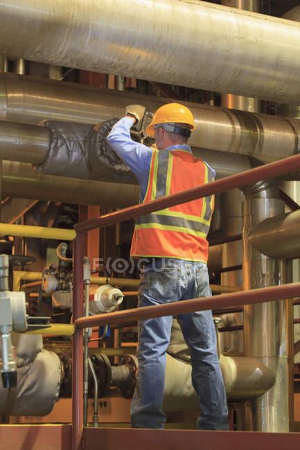Інженер на електростанції, що налаштовує ручний клапан у трубопроводі конденсатору. — стокове фото