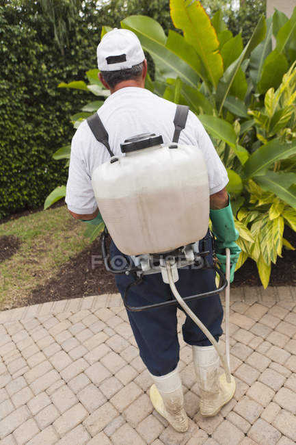 Técnico de control de plagas con rig de pulverización portátil usando manguera de pulverización. - foto de stock
