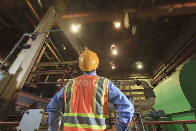 Engineer in electric power plant studying movement of overhead crane — Stock Photo