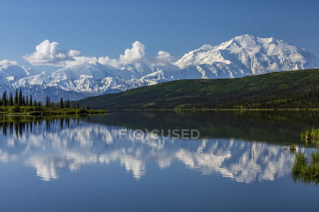 Denali shows well with the blue waters of Wonder Lake, Denali National Park and Preserve, Interior Alaska; Alaska, United States of America — Stock Photo