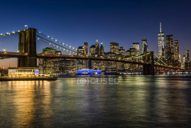 Manhattan skyline y Brooklyn Bridge at twilight, Brooklyn Bridge Park; Brooklyn, Nueva York, Estados Unidos de América. - foto de stock