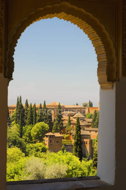 Arched window with a view from Alhambra; Granada, Andalusia, Spain — стоковое фото