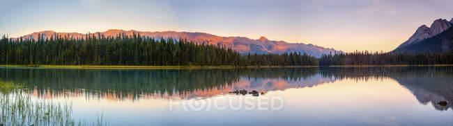 Tranquil lake with reflections in Elk Lakes Provincial Park at sunset; British Columbia, Canada — стокове фото