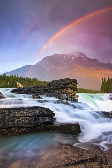 Double rainbow shining over a rugged waterfall and the Rocky Mountains, Jasper National Park; Alberta, Canada — стоковое фото