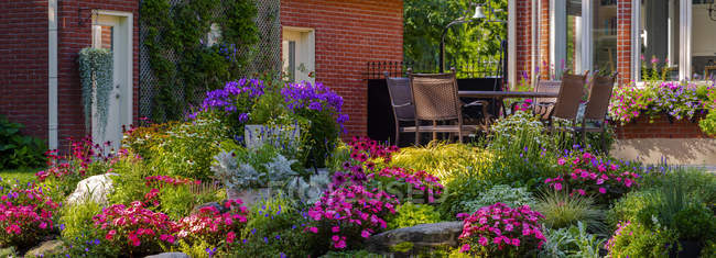 Blossoming flowers in a garden in a residential backyard with patio furniture; Hudson, Quebec, Canada — Stockfoto