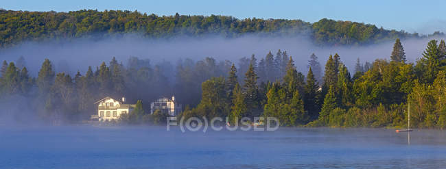 Mist laying over Lac a la Truite at dawn with low clouds hanging over the forest along the shoreline; Quebec, Canada — Photo de stock