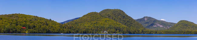 Lake Superior with tree-covered hills and a bright blue sky; Lac Superieur, Quebec, Canada — Photo de stock