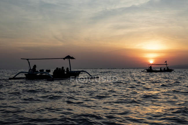 Indonesian jukung, traditional wooden outrigger canoe at sunrise; Lalang, Bali, Indonesia — Stock Photo