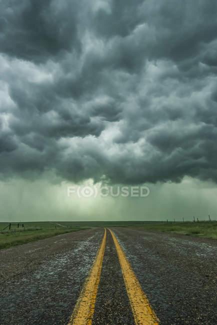 Пустой шоссе исчезает в устье шторма где-то в Техасе Panhandle; Техас, Соединенные Штаты Америки — стоковое фото