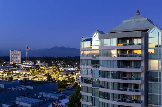 Edificio residenziale al crepuscolo con una bandiera canadese e montagne in lontananza; Surrey, Columbia Britannica, Canada — Foto stock
