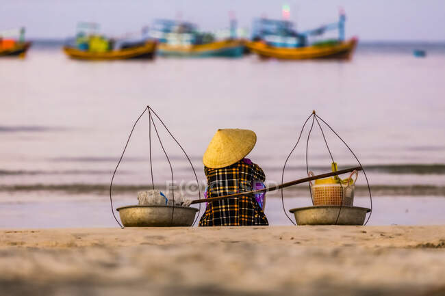 Una mujer sentada en la playa con vistas a los numerosos barcos de pesca en el agua frente a la costa, Ke Ga Cape; Ke Ga Island, Vietnam - foto de stock