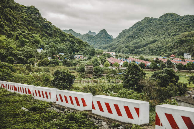 Barriers across the landscape with a town and lush foliage covering the karst limestone formations; Cat Ba island, Vietnam — Stock Photo