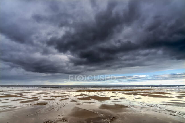 Nuages de tempête foncés au-dessus de l'océan Atlantique avec plage de sable humide au premier plan ; South Shields, Tyne and Wear, Angleterre — Photo de stock