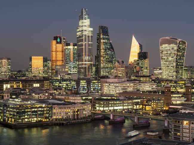 Stadtbild und Skyline von London in der Abenddämmerung mit 20 Fenchurch, 22 Bishopsgate und verschiedenen anderen Wolkenkratzern und der Themse im Vordergrund; London, England — Stockfoto