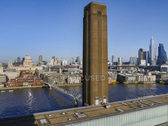 Cheminée de la Tate Modern art museum and the Millennium Bridge crossing the River Thames with a cityscape of London ; Londres, Angleterre — Photo de stock