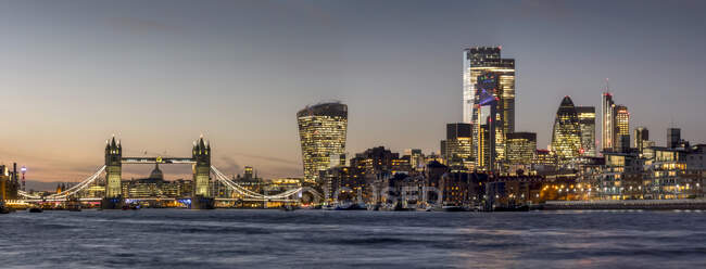 Cityscape and skyline of London at dusk with 20 Fenchurch, 22 Bishopsgate, and various other skyscrapers, and the River Thames in the foreground; London, England — Stock Photo
