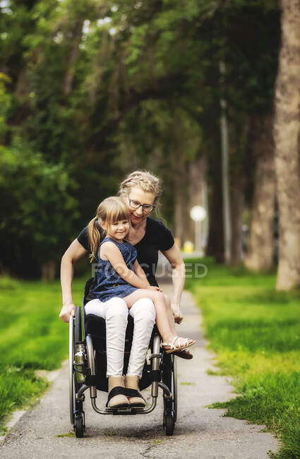 Eine querschnittsgelähmte Mutter hält ihr kleines Mädchen auf dem Schoß, während sie an einem warmen Sommernachmittag mit ihrem Rollstuhl die Straße hinunterfährt: Edmonton, Alberta, Kanada. — Stockfoto