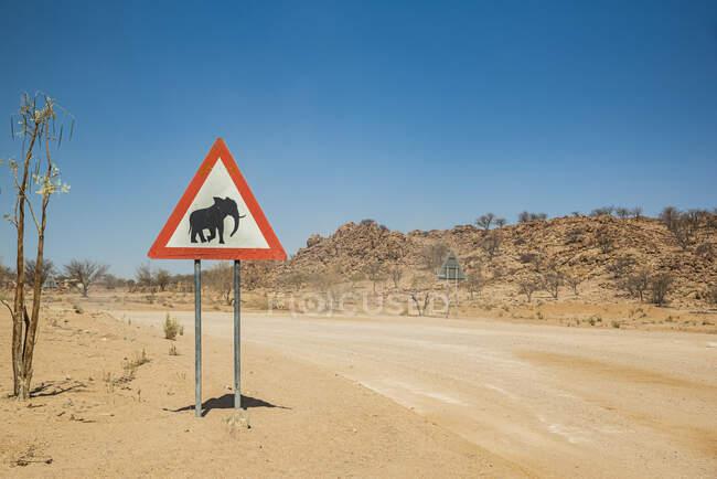 Предупреждающий знак слона на обочине дороги, по дороге к горе Брандберг, Дамараланд; регион Кунене, Намибия — стоковое фото