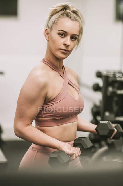 Mujer haciendo ejercicio con pesas; Wellington, Nueva Zelanda - foto de stock