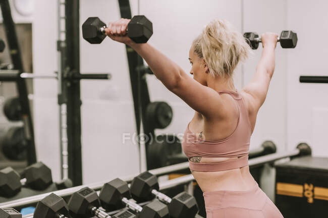 Woman working out with weights; Wellington, New Zealand — Stock Photo