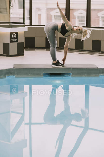 Woman working out on a mat beside a pool; Wellington, New Zealand — Stock Photo