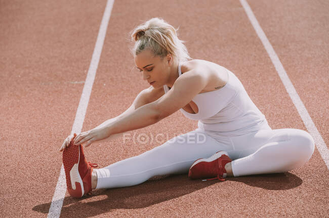 Mulher sentada para esticar os músculos da perna para se preparar para correr em uma pista; Wellington, Nova Zelândia — Fotografia de Stock