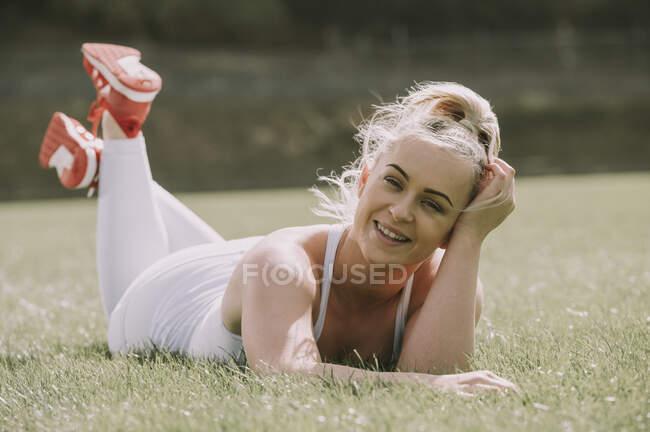 Giovane donna sdraiata su un campo di erba nel suo abbigliamento allenamento; Wellington, Nuova Zelanda — Foto stock