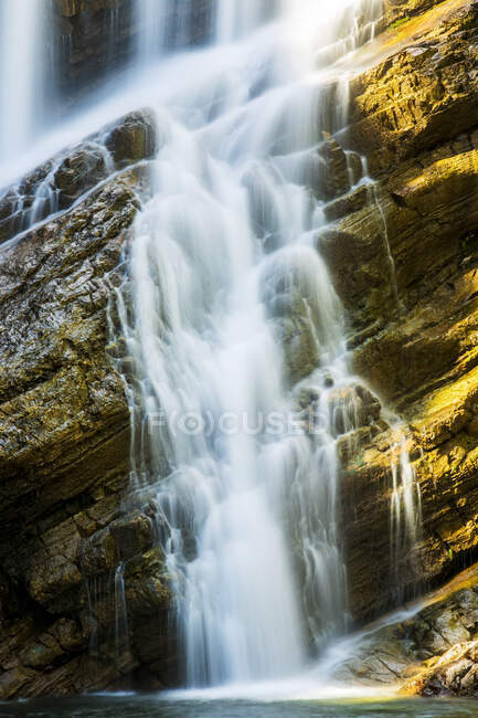 Close-up of waterfalls on angled rocky cliff, Waterton Lakes National Park; Waterton, Alberta, Canada — Stock Photo