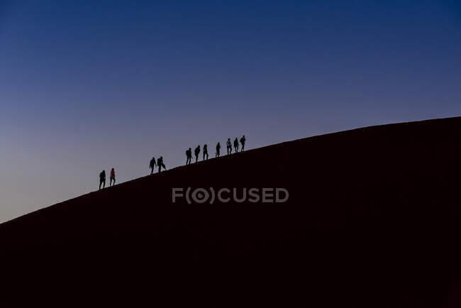 Силуэты туристов, восходящих на Дюну 45 в сумерках, Соссусвлеи, пустыню Намиб; Намибия — стоковое фото