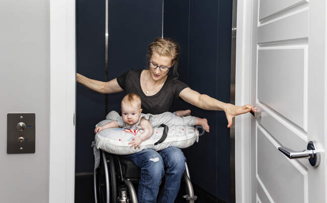 A paraplegic mother holding her baby on her lap while getting into her home elevator with her wheelchair: Edmonton, Alberta, Canada — Stock Photo