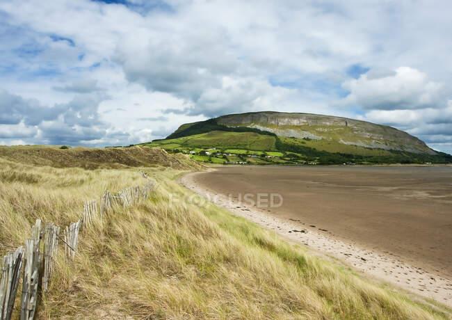 Costa irlandesa com grama de praia e maré retrocedida e cerca de madeira velha, com uma montanha planalto e falésias no fundo durante o verão; Strandhill, County Sligo, Irlanda — Fotografia de Stock