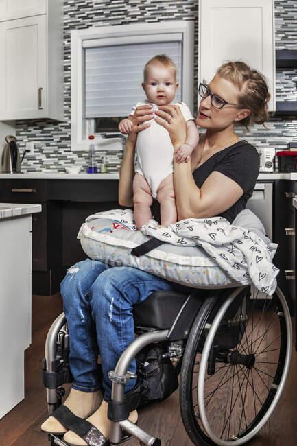 Une mère paraplégique tenant son bébé sur ses genoux, dans sa cuisine, alors qu'elle était assise dans son fauteuil roulant : Edmonton, Alberta, Canada — Photo de stock