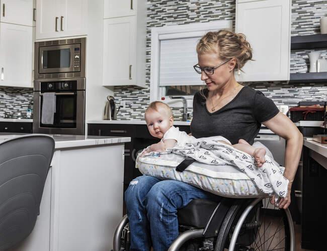 Парализованная мать, держащая своего ребенка на коленях, на кухне, в инвалидном кресле: Эдмонтон, Альберта, Канада — стоковое фото