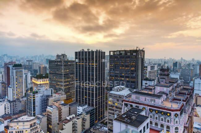 Wolkenkratzer unter leuchtend orangen Wolken bei Sonnenuntergang; Sao Paulo, Sao Paulo, Brasilien — Stockfoto