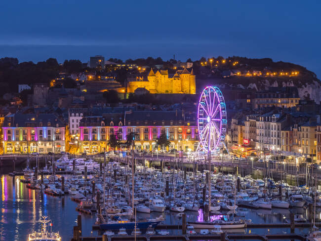 Harbour full of boats and an illuminated ferris wheel at night with lights illuminating the Chateau de Dieppe castle on the hillside; Dieppe, Normandy, France — Stock Photo