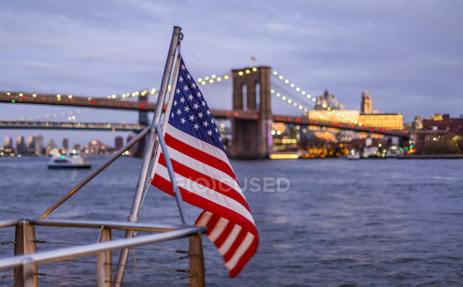 Drapeau américain agitant une rampe au bord de l'eau avec vue sur le Brooklyn Bridge, Manhattan ; New York City, New York, États-Unis d'Amérique — Photo de stock