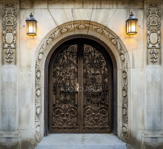 Ornate double doors with decorative carvings on the walls and mounted lit sconces; New York City, New York, United States of America — Stock Photo