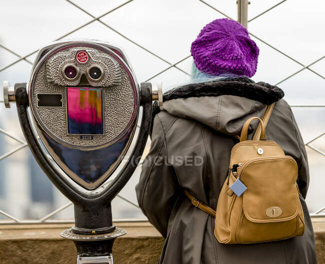 Female tourist standing beside binoculars outside on the observation deck at the Empire State Building in Midtown Manhattan; New York City, New York, United States of America — Stock Photo