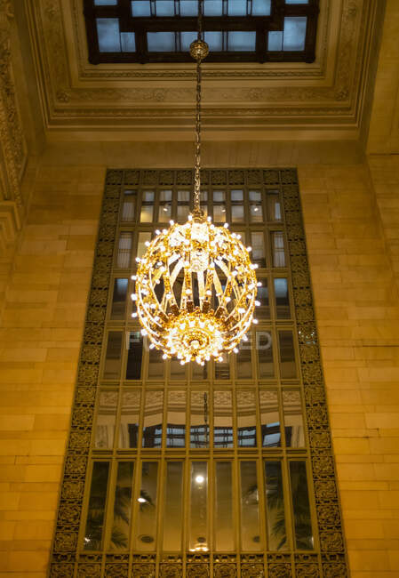 Illuminated and decorative round chandelier hanging in front of a mirror in a Manhattan building; New York City, New York, United States of America — Stock Photo