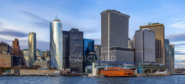 Downtown New York City y el ferry Staten Island en Whitehall Terminal; New York City, New York, Estados Unidos de América - foto de stock
