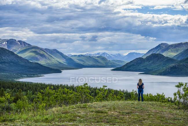 Mulher de pé e olhando para um lago e as vastas cordilheiras Yukon; Whitehorse, Yukon, Canadá — Fotografia de Stock
