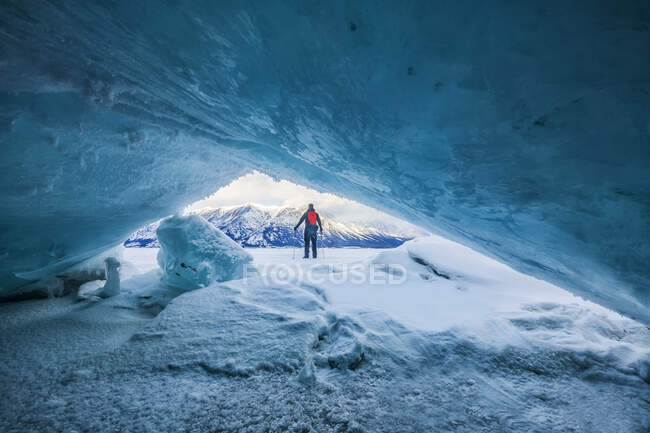 Man with trekking poles standing looking out at the frozen lake; Haines Junction, Yukon, Canada — Stock Photo