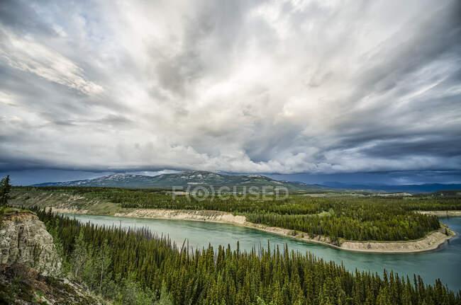 Река Юкон с бурей, проходящей над головой, протекая через Уайтхорс; Уайтхорс, Юкон, Канада — стоковое фото