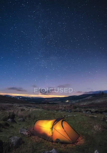 Зажженная палатка, разбитая по ночам в горах со звездами в небе; графство Хемпшир, Ирландия — стоковое фото