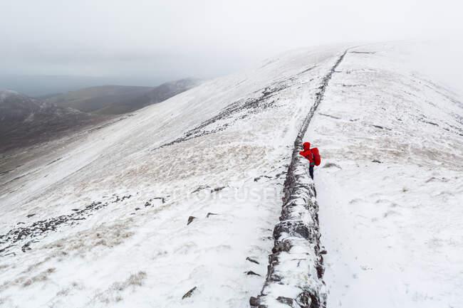 Escursionista di sesso femminile che si affaccia su un vecchio muro di pietra in cima alle Galty Mountains in inverno con tempo nuvoloso e nebbioso; Contea di Tipperary, Irlanda — Foto stock