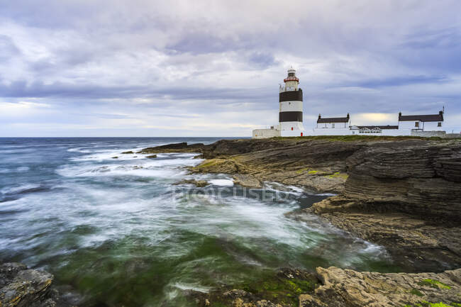 Hook Head lighthouse, Black and white lighthouse on rocky shore on a cloudy summer day, long exposure; County Waterford, Ireland — Stock Photo