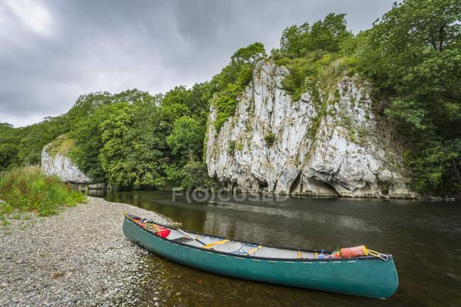 Un canot vert sur la rive de la rivière Blackwater à Cork avec des falaises blanches sur la rive opposée en été ; Killavullen, comté de Cork, Irlande — Photo de stock