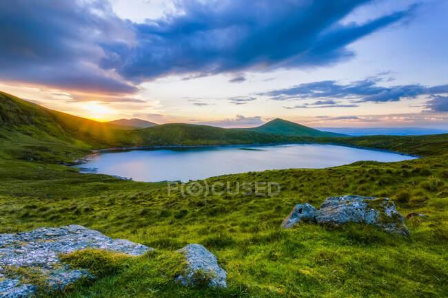 Солнце садится над Lough Muskery в Galty Mountains летом с большими валунами на переднем плане, Galty Mountains; графство Лимерик, Ирландия — стоковое фото